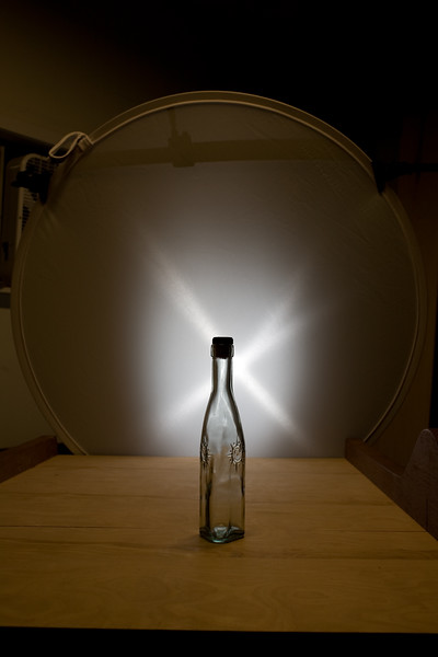 Here I have placed my diffuser directly behind the bottle and the flash zoomed to a narrow beam behind it. Exposure is set for the surface of the diffuser which is very bright, so the flash set to 1/128 power to allow an f/8 aperture.<br /> <br /> The cross in the light pattern is created by the fresnel lens in the flash at close range. That cross pattern is less than ideal for most photographs so normally I would elimiate it by using double diffusion of my light source. That, however, substantially increases the complexity of the setup.<br /> <br /> As a side note, the reason you pay good money for good quality softboxes is that they have an internal baffle specifically designed to smooth out any unevenness in the light source.