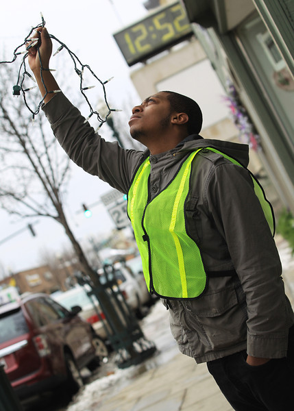 BGSU Student Marcus Huguley helps hold lights as they are being removed from trees on Main Street