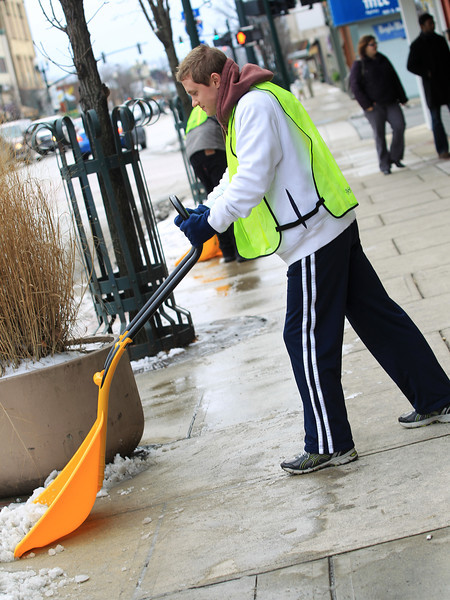 BGSU Student, David Denison helps shovel snow off of Main Street sidewalk