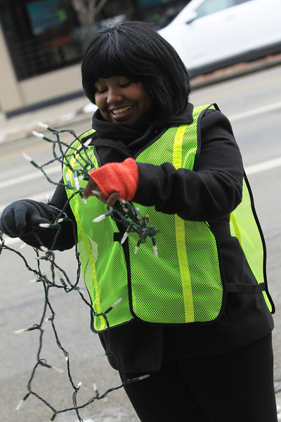 BGSU Student Angel Edwards helping remove lights from trees on Main Street