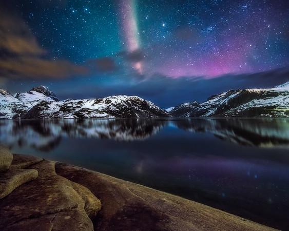 Photo of Aurora Borealis over a mountain lake in Norway