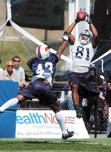 jhfinalpractice3 - Receiver Peerless Price leaps high in the air to catch a pass behind rookie cornerback Eric Bassey in 11-on-11 drills Thursday.