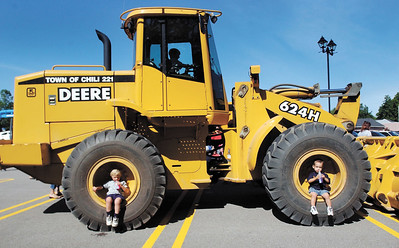 jhtrucks1 - Jonathan Fox 2,  and Evan Morse 2, both of Chili find a nice place to sit and enjoy a drink while they attended a Heavy Equipment and Tractor show at the Chili Public Library on Wednesday August 23.