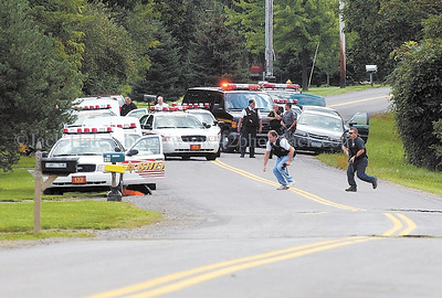 jhstandoff1 - Police officers cross LaRue Road in Manchester Tuesday afternoon to get into position.