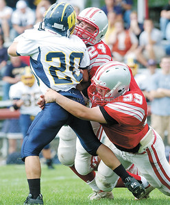 jhcawaynefb3 - Wayne runningback Steve Singley gets wrapped up by Michael Lundy and Jian Ou Ho in the second quarter.