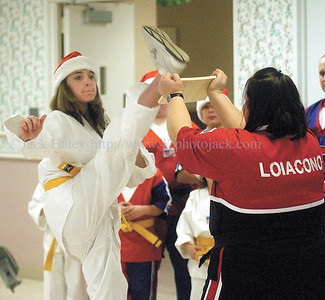 jhtaekwondo1 - Lindsay Loicono of the Loiacono Tae Kwon Do team from the Canandaigua YMCA holds a board as Jene Keeney breaks it with a kick during a demonstration for residents at the MM Ewing Continuing Care Center on Saturday