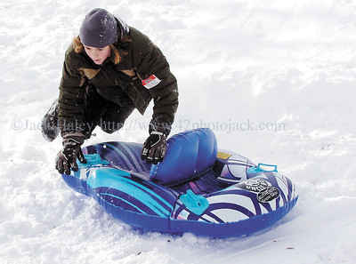 jhsled3 - Jonas Preston, 9, of Canandaigua looses contack with his snow tub after going over a jump on a downhill run at Baker Park in Canandaigua on Saturday, 1-20.