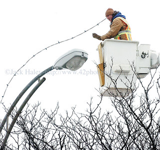 jhlightremoval2 - Steve Harwood of the City of Canandaigua Parks Department uses a bucket truck to help him remove Christmas Lights from the trees along South Main Street on Tuesday 1/31.