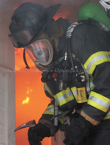 jhdrill3 - Canandaigua firefighter Bryan Kransler, the training officer, who ran the drill comes to the porch after setting a fire which will be extinquished as part of the drill.