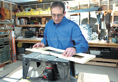 """jhhole1B - Ken Rieck of Hole In The Wall Products uses a router on a piece of wood which will eventually become a """"Paper Pantry"""" in his shop in Victor."""