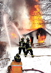 jhdrill1 - Firefighters spray a maple tree to keep it as the cottage is burned down on Saturday, January 27. All the trees that the homeowner requested to be saved, were saved.