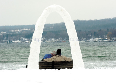 jhsnowarch1 - Andrew Kinsman (right) of Victor and Kathy Jabaut of Canandaigua take a break on a bench at Kershaw Park on Friday after building this snow arch.