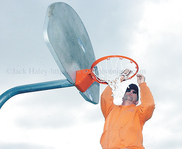 jhhoophanger2 - Randy Woodhams, Village of Shortsville, Public Works. maintenance supervisor works on the basket he put up at Budd Park on Wednesday (4-18). Hopefully springtime weather will come in and the basketball court and other fun activities can be enjoyed.