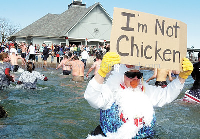 jhfreezefest2 - Marge Donhauser of Canandaigua might have been dressed like a chicken but her sign points out that she wasn't as she and dozen others jumped into the chilly waters on Saturday.