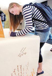 jhflcctribute1 - FLCC student MaryBeth Watson of Oneida signs a banner with thoughts and prayers from FLCC students which will be shipped to Virginia Tech to honor those slain in the recent killings.
