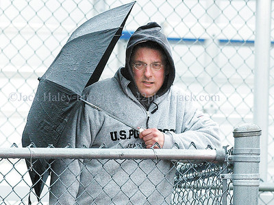 jhwetfan - A heavy downpour coupled with strong winds forced fans to try and stay dry like Patrick Bourcy of Penfield during the Spring Invitational Track Meet at Victor on Thursday (4/12).