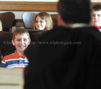jhmocktrial1 - Newerk fifth grader Ryan Tracy chuckles as he answers questions by Ontario County Court Judge Craig Doran before being accepted as a juror in the mock trial involing students from Newark, Naples and Canandaigua on Friday 4-27.