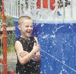 jhsulphur2 - Joshua Tubbs, 8, of Phelps finds a way to cool off on a hot day, stand next to the dunking tank and wait for the person to get dunked. That's what he did on Saturday afternoon at the Sulphur Springs Festival on Saturday, June 2.