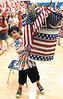jhmemorial1 - Second grader Adam Baghi helps out by taking a bucket full of flags used by Midlakes 1st graders induring their Memorial Day Program on Friday.