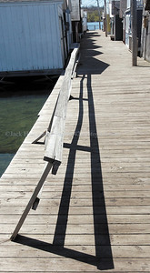 jhshadows - Shadows that are straight, curved and pointed fall along a row of boathouses on the City Pier in Canandaigua, on Thursday 5/3.