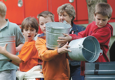 jhhomestead1 - Canandaigua second graders (L-R) Malcolm Ivers, Chris Ayers and Tyler Gibeau get a bit backed up with buckets as the students learned what a firefighting bucket brigade was likefor 19th-Century folks at the Granger Homestead on Thursday, June7.