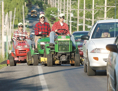jhlawnboys1 - CA seniors (l-r) Brendan Ewing, Jim Baker, and Jake VanBuren ride thier riding lawn mowers up Chapel Street to school on Tuesday, June 12.