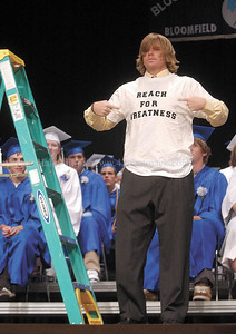 jhbloomgrad2 - Jacob Warner dressed in a cap and gown to  present his Commencement Speech,  then used a trophy, ladder and T-shirt to end his speech.