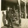 Man with pet raccoon, beer barrels in background, ca. 1910.  RPPC