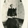 Elderly woman looking at photo album, ca. 1915.  RPPC