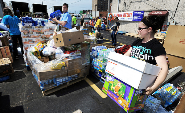 Globe/T. Rob Brown<br /> Kimberly Ward (right), a Central Christian Center church member who lost her apartment in the tornado, helps unload a group of tractor trailers Friday morning, May 27, 2011, outside the downtown Joplin church. The non-denominational church has been receiving large donations from many faith-based organizations including Utah Cares.