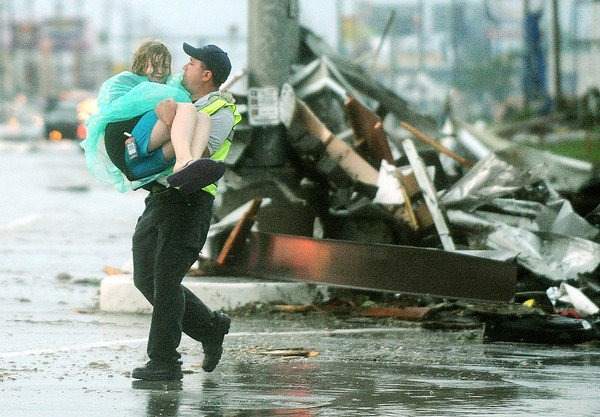 Globe/Roger Nomer<br /> Joplin Police Sgt. Gabe Allen carries a girl to safety from the remains of Academy Sports along Range Line Road on Sunday evening.