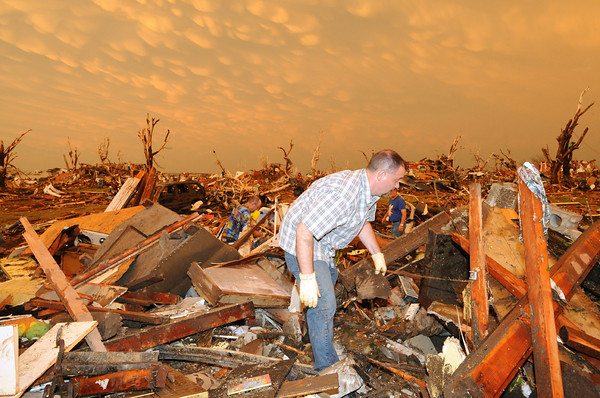 Globe/B.W.Shepherd<br /> A man is looks through the rubble of his destroyed home near 20th and Connecticut 1 1/2 hours after an EF-5 tornado destroyed Joplin on Sunday evening, May 22, 2011. An orange sunset illumated the evening sky.