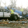 Globe/Roger Nomer<br /> An emergency worker searches through damaged cars along Range Line Road on Sunday evening.