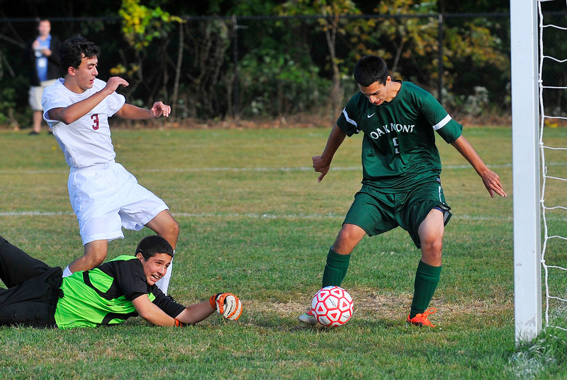 Oakmont's Charles Pappas gets a shot off for a goal by Fitchburg goalie Joey Pepoli and Joshua Veronesi during Monday's game.<br /> SENTINEL & ENTERPRISE / BRETT CRAWFORD