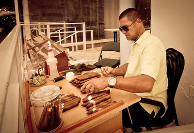 Wednesday, May 2, 2012. A man rolls cigars along Ocean Drive on South Beach in Miami.