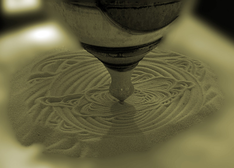 July.8,2006  <U>Sands of time</U>  This was extremely interesting to watch. That pot thingy was hung from a string, and was making all sorts of interesting patterns on the sand just below it.  Still learning how to do sepia tones well and ofcourse, the blur too!