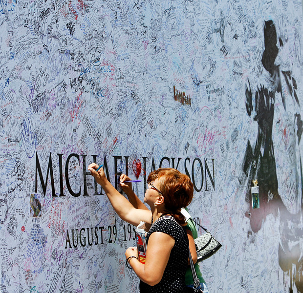 Fans sign a large Michael Jackson poster outside Staples Center in Los Angeles July 6, 2009. The memorial for the pop star will be held at Staples Center in Los Angeles July 7.  REUTERS/Mario Anzuoni   (UNITED STATES ENTERTAINMENT OBITUARY)