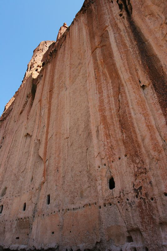 Example of a shear cliff face. Note the rows of horizontal holes in the face of the cliff. These were used to support lodge poles that extended over the roof of the houses built in front of the cliffs. Rooms were dug into the cliffs for storage.