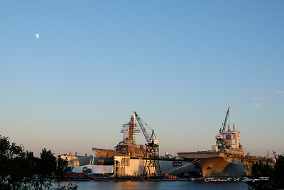 Navy ships in dry dock under a 3/4 moon