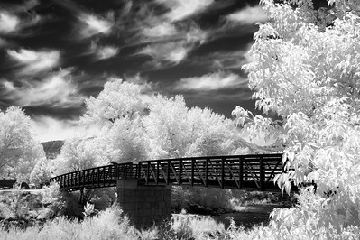 The footbridge in Durango, Colorado spans the Animas river, parallel to the train trestle and tracks.  Captured in infrared.