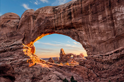 The Turret Arch viewed through the Window Arch in Arches National Park at sunset.