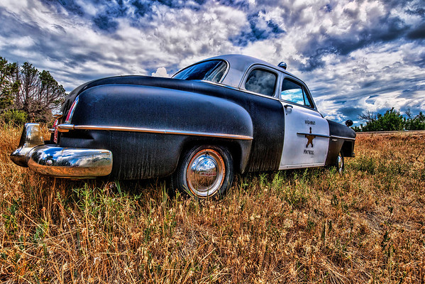 In Bayfield, Colorado an out-of-use Sheriff car was parked in the summer grass.