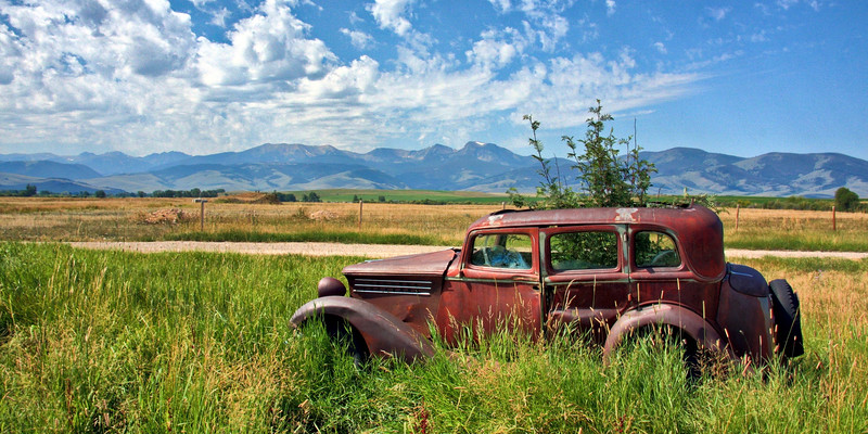 An antique car 'planter' sits near Harrison with a Tabacco Root mountains backdrop.