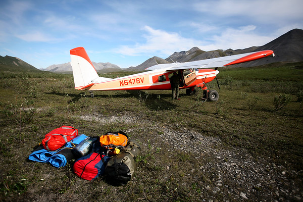 KONGAKUT RIVER HEADWATERS, AK - Helio pilot Ken puts the seat back into the plane. The seat has to come out to access the cargo space avaliable in the Helio Courier.