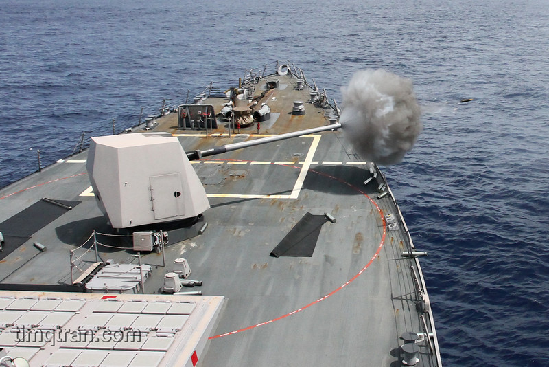 """Fire for Effect!""<br /> USS Mustin (DDG 89) fires her 5 inch gun  while conducting Naval Surface Fire Support (NSFS) qualifications.  The ship fired at land targets to practice supporting an amphibious invasion."