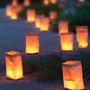 Candle powered Christmas luminaries line a pathway at dusk.
