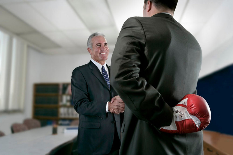 Two executives shake hands but one is planning mischief.