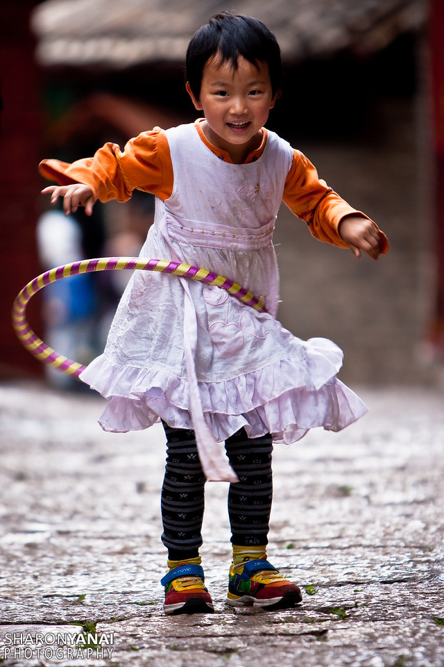 Little girl playing the Hula Hoop on the sreets on Lijiang, China