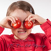 Pre-schooler girl holding two tomatoes to her eyes.