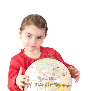 Pre-schooler girl with globe isolated on white.